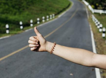 Ausgestreckter Arm mit Daumen nach oben auf einer Landstraße